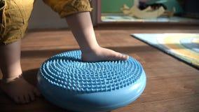 Den lilla ungen masserar hans fot, medan stå på filten stock video