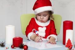 Den lilla ungen skrivar brevet till jultomten fotografering för bildbyråer