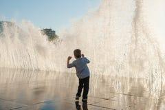Den lilla ungen vänder mot fearfully en gigantisk våg vid havet i staden fotografering för bildbyråer