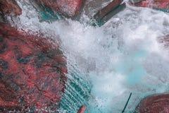 Den lilla vattenfallet i förgrunden med vaggar av röda signaler och kristallklart vatten av blåa färger arkivbild