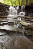 Den lilla vattenfallet med i lager vaggar i träna Arkivbild