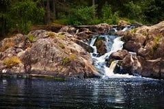 Den lilla vattenfallet och vaggar i skog i Karelia Royaltyfria Foton