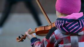 Den lilla violinisten spelar på gatorna av staden arkivfilmer