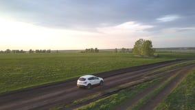 Den lilla vita bilen flyttar sig exakt längs den smala smutsiga vägen stock video