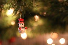 Den lilla vita snögubben i röd hatt på julen gör grön trädet Royaltyfri Bild