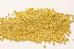 Guld- pryder med pärlor på vit Arkivfoto