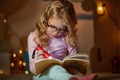Den lite intresserade ungen är läseboken i barnkammare Royaltyfria Bilder