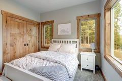 Den liten ändå slags tvåsittssoffasovruminre presenterar vit säng med huvudgaveln royaltyfri fotografi