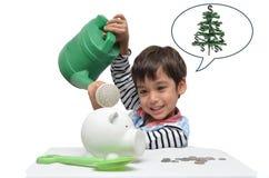 Den Litlle ungen som bevattnar spargrisen för mer pengar, växer upp Arkivbilder