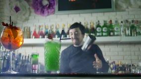 Den ljusa alkoholdrycken med nya jordgubbar står på stångtabellen och på bakgrund av barkeeperen utför jonglerar med lager videofilmer