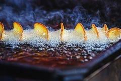 Den ljusa bilden av den smakliga skorpan som bildar på spiral, klippte potatisar som steker i olja arkivfoto