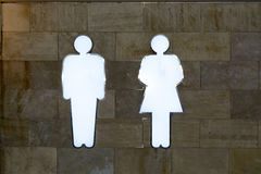 Den ljusa handboken i WSEN - forma män och kvinnor, glödande vitt neon på väggen Royaltyfri Bild