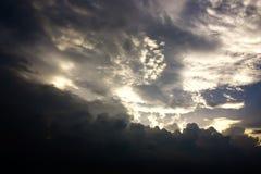 Den ljusa himlen över de svarta åskamolnen Royaltyfri Bild