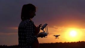 Den ljusa kvinnan rymmer en panel för att fungera hennes surr på solnedgången i slo-mo lager videofilmer