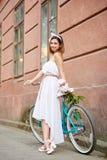 Den ljusa kvinnlign lutar på den retro cykeln med bukettpioner royaltyfri fotografi