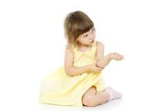 Den ljusa liten flicka sitter royaltyfria foton