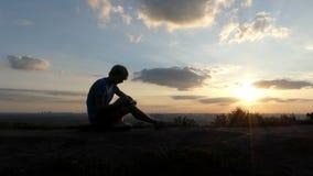 Den ljusa mannen skriver en saga på en gräsmatta på solnedgången i slo-mo arkivfilmer