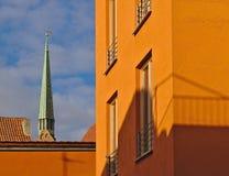 Den ljusa orange fasaden av modern bostads- byggnad tände vid aftonsolen med den kyrkliga tornspiran i bakgrunden arkivbild