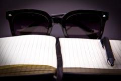 Den ljusa pappers- notepaden med den svarta bokmärken och pennan fokuseras i en mitt Arkivbild