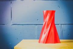 Den ljusa röda objektvasen skrivev ut vid skrivaren 3d på den blåa tegelstenväggen Royaltyfri Fotografi