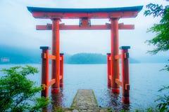 Den ljusa röda Torii porten doppade i vattnet av Ashi sjön, caldera med berg på bakgrunden Hakone relikskrin arkivfoto