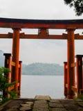 Den ljusa röda Torii porten doppade i vattnet av Ashi sjön, caldera med berg på bakgrunden Hakone relikskrin royaltyfria foton