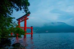 Den ljusa röda Torii porten doppade i vattnet av Ashi sjön, caldera med berg på bakgrunden Hakone relikskrin, Kanagawa pref royaltyfri foto