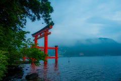 Den ljusa röda Torii porten doppade i vattnet av Ashi sjön, caldera med berg på bakgrunden Hakone relikskrin, Kanagawa pref royaltyfria foton