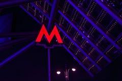 Den ljusa röda tunnelbanaingången suckar i Moskva på nigh royaltyfri foto