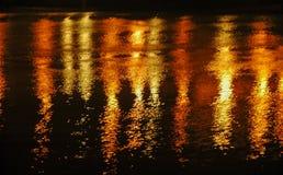 Den ljusa reflexionen på vatten på natten i röd guling ser nästan som fyrverkerier fotografering för bildbyråer