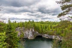 Den ljusa sjön är ett tidigare villebråd, var marmor bröts under en blå himmel med moln, Karelia Ryssland arkivfoton