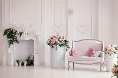 Den ljusa soffan med rosa kuddeställningar i det inre ljusa studiorummet nära den romantiska spisen dekorerade med våren Royaltyfria Foton
