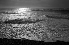 Den ljusa solen reflekterar av vitt skum på stranden som vågor bryter av royaltyfri foto