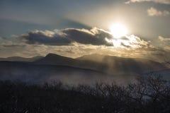 Den ljusa solpiercingen fördunklar i de Catskill bergen royaltyfria bilder