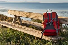 Den ljusa turist- ryggsäcken ligger på bänken som lokaliseras på mouen Royaltyfria Foton