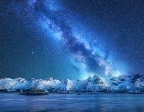 Den ljusa Vintergatan över snö täckte berg och havet på natten royaltyfri foto