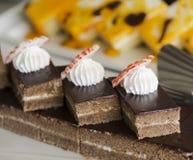 Den ljusbruna kakan dekorerade med kräm på den vita plattan Selektivt fokusera Royaltyfria Bilder