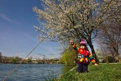 Den ljust färgade flickan låtsar för att fiska under ett blomstra träd Arkivbilder