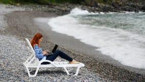 Den ljust rödbrun frilans- affärskvinnan sitter på Pebble Beach och arbetar på nytt sommarprojekt lager videofilmer