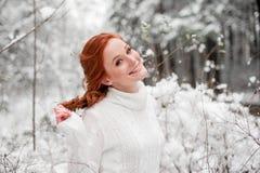 Den ljust rödbrun le kvinnlign i den vita tröjan i vinterskogsnö december parkerar in Stående Gullig tid för jul royaltyfri bild