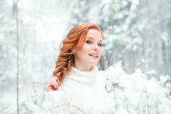 Den ljust rödbrun söta flickan i den vita tröjan i vinterskogsnö december parkerar in Stående Gullig tid för jul Fotografering för Bildbyråer