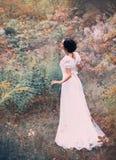 Den ljuva prinsessan i en lång vit klänning får förlorad i en avlägsen skog, lyssnar till oväsenet och sjunga av fåglar royaltyfri bild