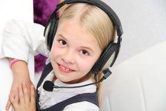 Den Llittle flickan sitter framme av en bärbar dator med hörlurar och lär Royaltyfri Bild