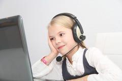 Den Llittle flickan sitter framme av en bärbar dator med hörlurar och lär Arkivfoto