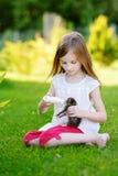 Den Llittle flickan som matar den lilla kattungen med, mjölkar Arkivfoton