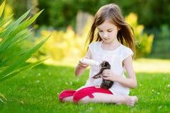 Den Llittle flickan som matar den lilla kattungen med, mjölkar Arkivbilder