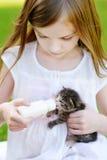 Den Llittle flickan som matar den lilla kattungen med, mjölkar Royaltyfria Foton