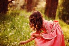 Den lockiga barnflickan i rosa sammankomst för sagaprinsessaklänning blommar i skogen Arkivfoton