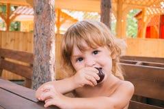 Den lockiga blonda flickan äter en läcker plommon utomhus Royaltyfria Bilder