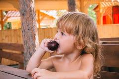 Den lockiga blonda flickan äter en läcker plommon utomhus Royaltyfria Foton